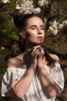 Geweldige brunette vrouw poseren in de buurt van de bloeiende magnoliaboom in trendy jurk