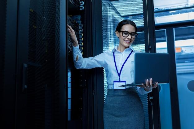 Geweldige dag. gelukkige mooie vrouw die in een serverkabinet werkt en haar laptop vasthoudt