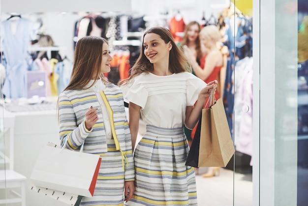Geweldige dag om te winkelen. twee mooie vrouwen met tassen kijken elkaar met een glimlach tijdens het wandelen in de kledingwinkel