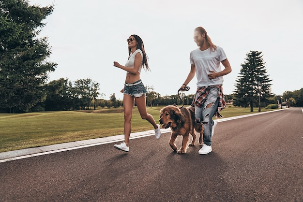 Geweldige dag samen. volledige lengte van een mooi jong stel dat met hun hond rent terwijl ze tijd buitenshuis doorbrengen
