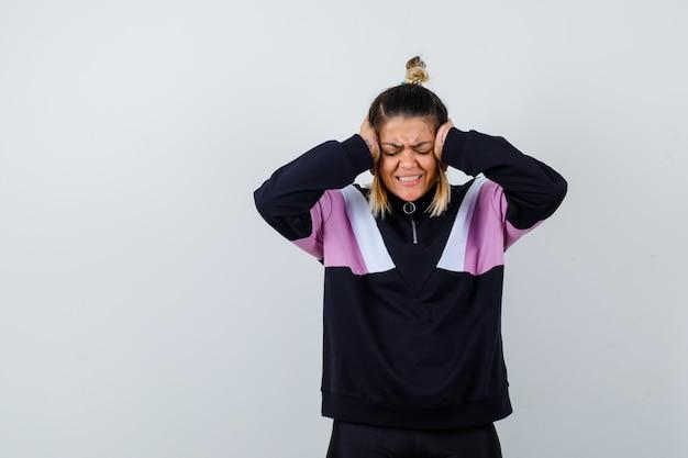 Geweldige dame in sweatshirt die de handen op het hoofd houdt terwijl ze de ogen sluit en er gestrest uitziet