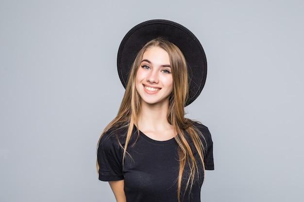 Geweldige dame met gouden haar gekleed in zwart met retro hoed glimlacht geïsoleerd op achtergrond