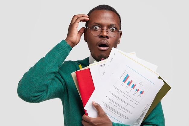 Geweldige donkere ondernemer draagt papieren met grafische diagrammen verrast door een laag inkomen van het bedrijf, controleert het financieringsplan, draagt een bril