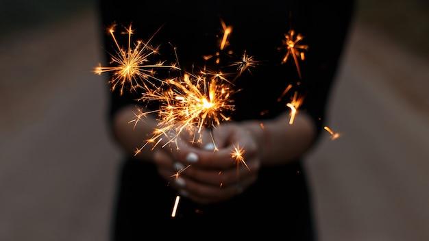 Geweldige feestelijke wonderkaarsen in de handen van een jonge vrouw