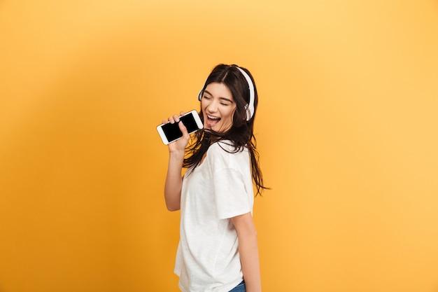 Geweldige gelukkig schattige jonge mooie vrouw luisteren muziek met koptelefoon zingen in de telefoon.
