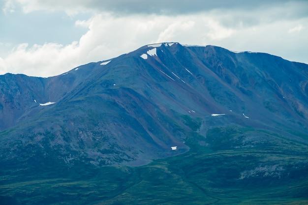 Geweldige gigantische berg met sneeuw bovenop in mist bij bewolkt weer.