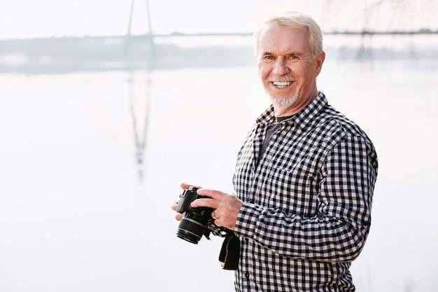 Geweldige hobby. vrolijke volwassen man camera dragen en glimlachen naar de camera
