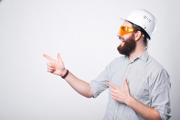 Geweldige ingenieur witte helm dragen en beschermende bril wijzend op copyspace
