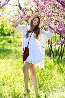 Geweldige jonge aantrekkelijke vrouw in witte lichte jurk met lang haar, in hoed wandelen in zonnige tuin op zomertijd. bloeiende sakura, lichte kleuren, camera kijken, stijlvol gevoelig model, relax