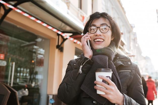 Geweldige jonge aziatische man koffie drinken en praten via de telefoon.