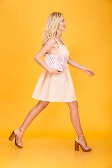 Geweldige jonge blonde vrouw met cadeau.