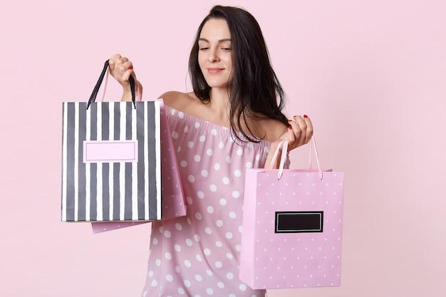 Geweldige jonge brunette vrouw draagt polka dot jurk, poseert met boodschappentassen en kijkt neer met peinzende gezichtsuitdrukking, staande op roze, heeft een verjaardagscadeau.