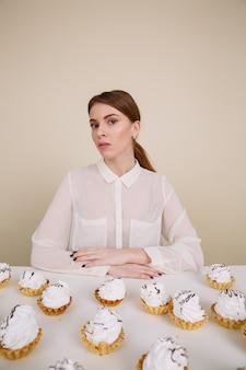 Geweldige jonge dame poseren zittend in de buurt van cupcake
