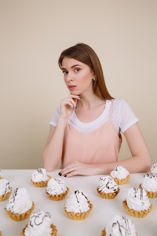 Geweldige jonge dame zitten en poseren in de buurt van cupcakes