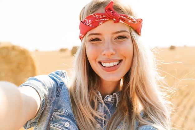 Geweldige jonge gelukkig vrouw permanent op het veld poseren neem een selfie door camera.
