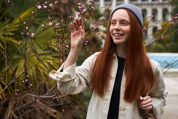 Geweldige jonge roodharige vrouw in hoed poseren in bloeiende boom in het voorjaar mooie gelukkige jonge vrouw e...