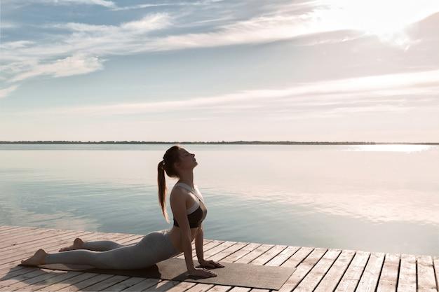 Geweldige jonge sportvrouw op het strand maakt yoga-oefeningen.