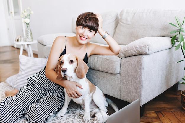 Geweldige jonge vrouw draagt gestreepte broek en polshorloge poseren op de vloer tijdens het spelen met beagle hond