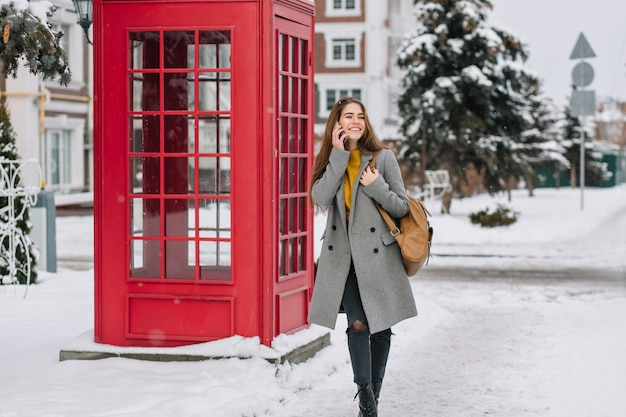 Geweldige jonge vrouw in grijze jas praten over de telefoon op straat. buiten foto van blije drukke vrouw met bruine tas loopt in de buurt van rode telefooncel.