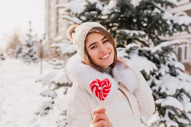 Geweldige jonge vrouw in witte warme kleren, gebreide muts met roze hart lolly met plezier op straat. aantrekkelijke vrouw genieten van wintertijd in de stad.