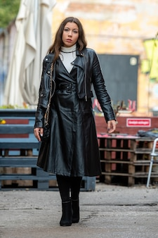 Geweldige jonge vrouw in zwart lederen kleding op een intreepupil terrasje