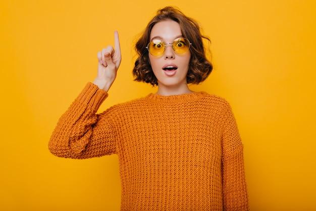 Geweldige jonge vrouw met lichtbruin haar poseren met geschokt gezichtsuitdrukking en vinger omhoog te houden