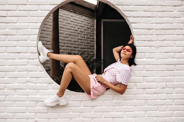 Geweldige jonge vrouw met tatoeage poseren op dichtgemetseld muur. buiten schot van brunette vrouw draagt witte sneakers.