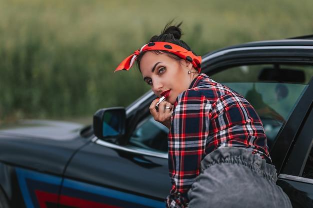 Geweldige jonge vrouw, portret in de buitenlucht, modieus model rijdende auto in haar casual sexy outfit, geweldig kapsel, make-up, hoge paardenstaart, gloeiende huid, safari-auto, volle roze lippen, spijkerbroek, geniet van haar reis