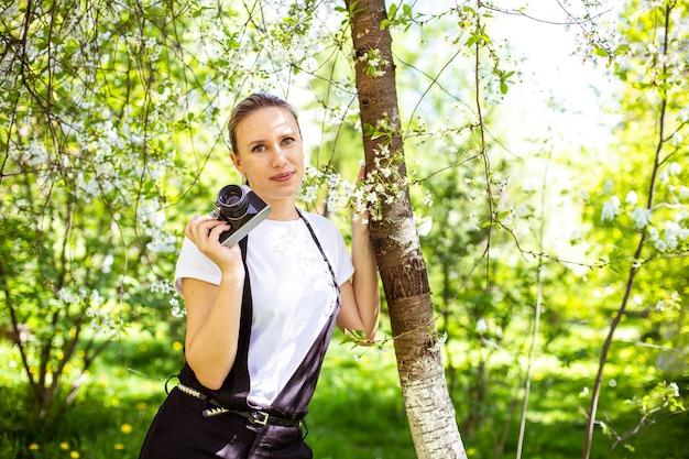 Geweldige jonge vrouw poseren in appelboom in het voorjaar