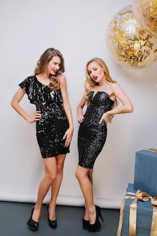 Geweldige jonge vrouwen in luxe zwarte jurken feest vieren. rode lippen, lang krullend haar, prachtige uitstraling, opgewekte stemming. groot cadeau, ballon met gouden tinsels, geweldig feest.