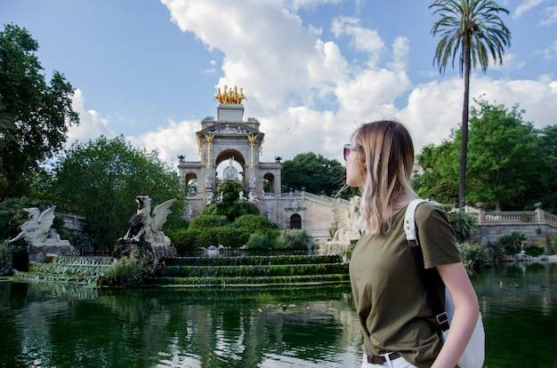 Geweldige jonge wonam in hebzucht t-shirt en witte tas op zoek op fontein van parc de la ciutadella, in barcelona, spanje. parkeer aan de noordoostelijke rand van ciutat vella, catalonië.