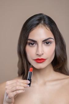Geweldige kleur, lippenstift. ernstige mooie jonge vrouw met bruine ogen en haren die felrode lippenstift tonen