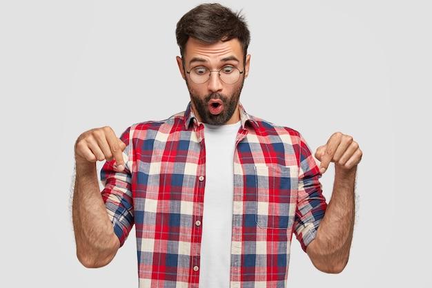 Geweldige knappe blanke man wijst met beide wijsvingers naar beneden, heeft een verbijsterde uitdrukking, merkt bedorven vloer op, draagt een wit t-shirt met een geruit overhemd, geïsoleerd over een witte muur.