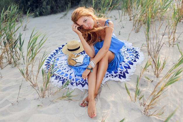 Geweldige lachende roodharige vrouw in blauwe jurk ontspannen op het zonnige voorjaar strand op handdoek. strohoed, stijlvolle armbanden en ketting.