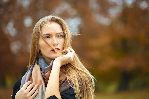 Geweldige langharige blonde vrouw met jas en sjaal, poseren in de botanische tuin. ruimte voor tekst