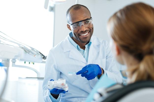 Geweldige leraar. aangename jonge mannelijke tandarts die zijn vrouwelijke patiënt uitlegt hoe tandplak te verwijderen tijdens het tandenpoetsen