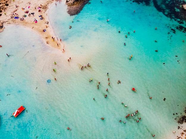 Geweldige luchtfoto van bovenaf over nissi beach in cyprus. nissi beach bij vloed. toeristen ontspannen op het strand. druk strand met veel toeristen. een populaire plek.