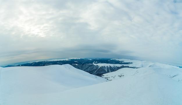 Geweldige luchtfoto van een heuvel bedekt met een dikke laag sneeuw op een bewolkte mistige dag. schoonheidsconcept van ongebruikelijke noordelijke aard. advertentie ruimte