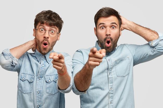 Geweldige mannen wijzen iets aantrekkelijks in de verte en dragen modieuze spijkeroverhemden