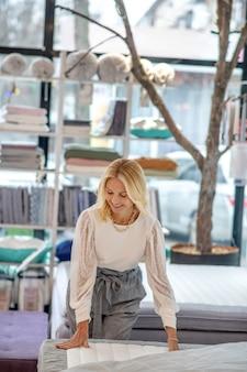 Geweldige matras. vrouw in een witte blouse die zich dichtbij het bed bevindt dat de matras bekijkt, die het met haar handen, in bewondering aanraakt.