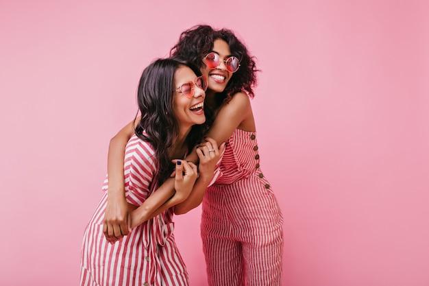 Geweldige, mooie dame verheugt zich en geniet van fotoshoot in roze. afrikaanse meisjes met krullend haar in zonnebril lachen.