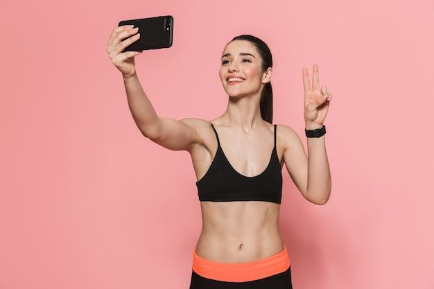 Geweldige mooie jonge mooie fitness vrouw met behulp van mobiele telefoon geïsoleerd over roze muur neem een selfie