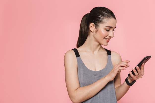 Geweldige mooie jonge mooie fitness vrouw met behulp van mobiele telefoon geïsoleerd over roze muur