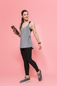 Geweldige mooie jonge mooie fitness vrouw met fles met water drinken geïsoleerd over roze muur