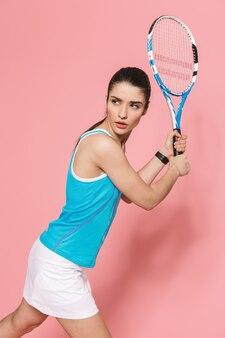 Geweldige mooie jonge mooie fitness vrouw met tennisracket poseren geïsoleerd over roze muur