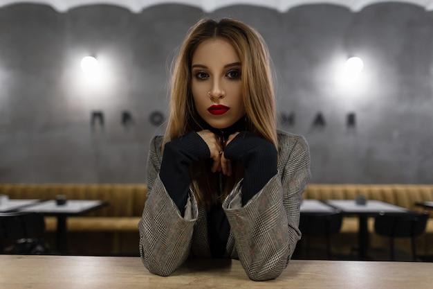 Geweldige mooie jonge vrouw met mooie make-up met rode lippen met een doorboorde neus in een grijs vintage geruit jasje in een zwart t-shirt zit aan een tafel in een café