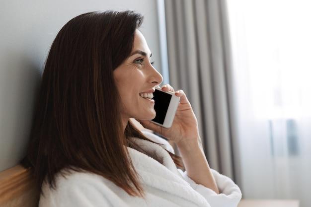 Geweldige mooie jonge zakenvrouw binnenshuis thuis praten via de mobiele telefoon.