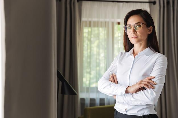Geweldige mooie jonge zakenvrouw in formele kleding binnenshuis thuis poseren.