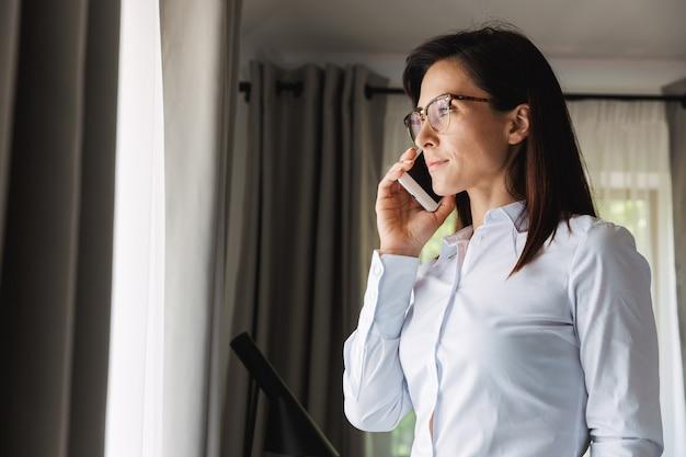 Geweldige mooie jonge zakenvrouw in formele kleding binnenshuis thuis praten via de mobiele telefoon.
