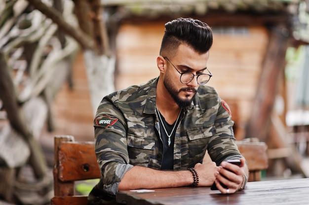 Geweldige mooie lange baard man in glazen en militaire jas buiten houten tafel van restaurant zitten en op zoek naar zijn telefoon